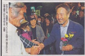 釈放され、たくさんの仲間に迎えられ、笑顔で握手する山城さん